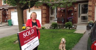 Maureen Bruce with Sold sign